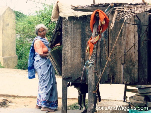 An elderly woman in a traditional sari, closing up shop